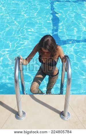Woman With Sexy Fit Body In Fashion Bikini, Swimwear Coming Out From Swimming Pool Water. Beautiful Fashionable Girl With Hot Body, Healthy Tan Skin In Swimsuit Posing With Pool Ladder In Summer.