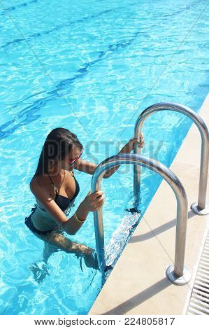 Beautiful sexy woman with perfect slim figure with long wet hair and bathing suit coming out of swimming pool on stairs swim, sunbathe have fun at beach party.