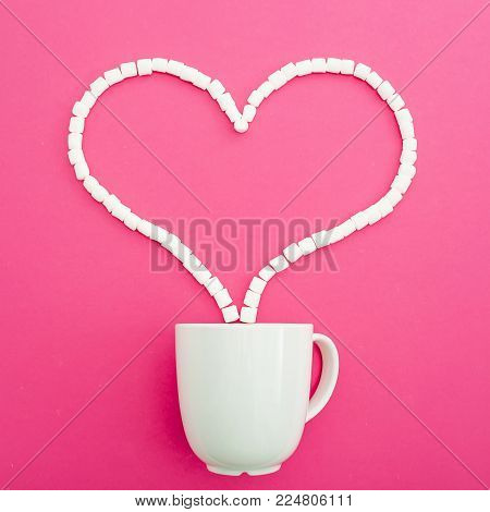 Valentines day concept. Heart made of marshmallows and coffee mug on pink background. Heart of candy. Flat lay. Top view