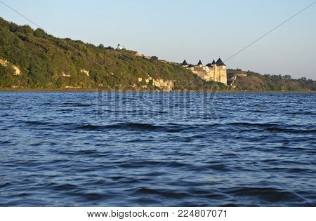 Landscape on the Dniester River with a view of the Khotyn Fortress. A lot of blue water in the foreground. And in the distance you can see the fortress, the castle Khotyn. Khotyn Nature Park
