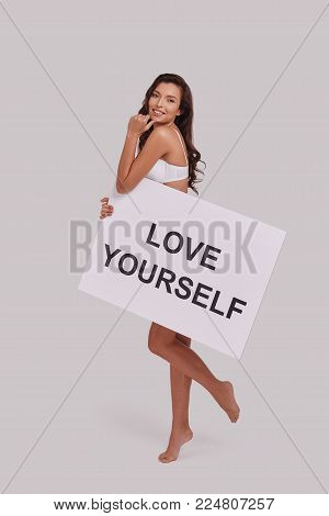 You deserve it!  Full length of attractive young smiling woman holding a poster and looking at camera while standing against grey background