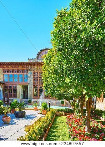 Shiraz, Iran - October 12, 2017: Zinat Ol-molk Mansion Boasts Scenic Green Garden With Flower Beds,