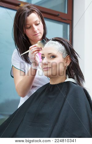 Haircare, relaxation and hairstyling concept. Woman sitting in black cape getting her hair colored by lady hairdresser in beauty salon