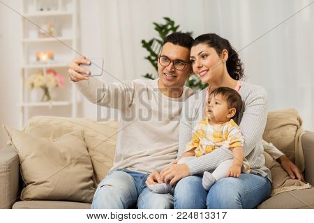 family, technology, parenthood and people concept - happy mother and father with baby daughter taking selfie by smartphone at home
