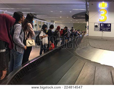 Kuala Lumpur, MALAYSIA - 31 December 2018: Passengers waiting in a baggage claim area.