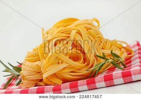 bundles of dried ribbon pasta on checkered place mat - close up