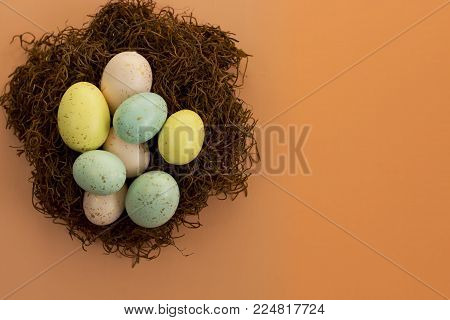 Gold speckled Easter eggs on a nest over a bright orange background.