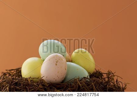 Close-up on some gold speckled Easter eggs in  nest, on a bright orange background.