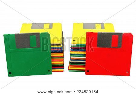 Horizontal shot of two stacks of old plastic multicolored disks.  A green disk is leaning against one stack and a red disk against the other.  Fronts showing.  White background.