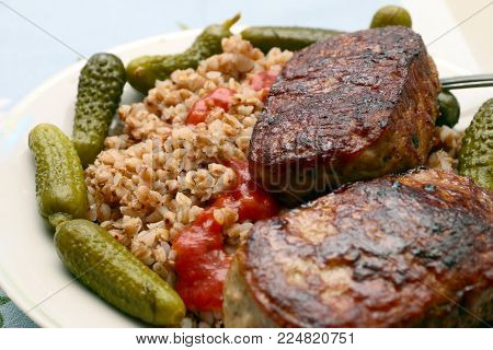 meat cutlets and garnish with buckwheat with pickled cucumbers