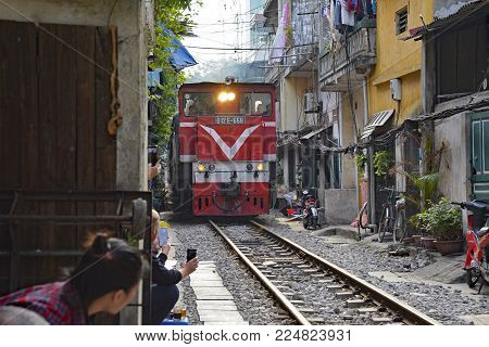 Hanoi, Vietnam - 16th December 2017. Tourists take photographs of the 15.30 train from Hanoi to Sapa as it goes along a residential street in central Hanoi which has grown up around the north-bound train track. The street is often referred to as train str