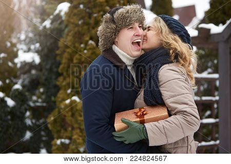 Man is hides box behind his back and going to give his woman a present on Valentine's Day, Christmas or New Year. Boyfriend and girlfriend dating romance. Husband gives gift to wife on her birthday. Celebration Theme.