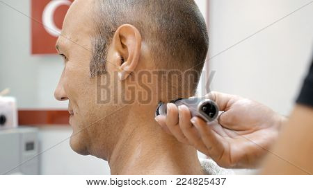 The barber is shaving his client in old fashion manner. Single blade shave gives the best result. Grooming is necessary for men and woman.