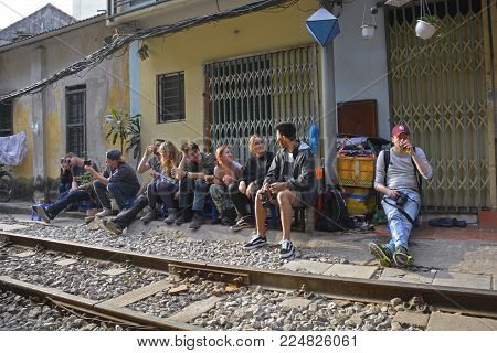 Hanoi, Vietnam - 16th December 2017. Tourists wait to see the 15.30 train from Hanoi to Sapa pass along what is commonly known as Train Street. This residential street in central Hanoi has grown up around the north-bound train track