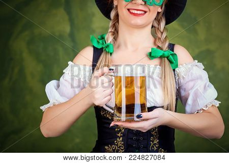 Girl waitress oktoberfest in national costume with a mug of beer in her hand. St. Patrick's Day.