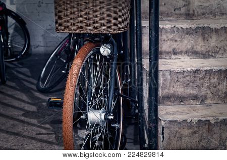 Closed bicycle in a cellar with a concrete staircase in a residential building to illustrate the parking of a bicycle without supervision in the basement, where it can be easily stolen