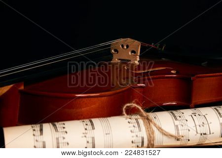 Violin and music notes. Rolled paper music sheet and classical violin isolated on black background with copy space, close-up.