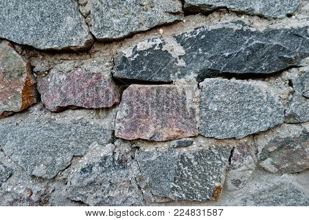 large wall of natural granite stones of different size and color, gray texture on a summer day, multi-colored granite natural stone, pieces of stone, splinters, texture pattern, stone wall, masonry