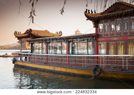 Chinese wooden floating restaurant moored near West Lake coast. Famous park in Hangzhou city, China