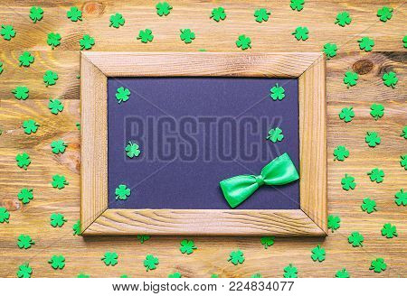 St Patricks Day festive background - wooden frame with green bow tie and free space for St Patricks Day text and green quatrefoils on the wooden surface. St Patricks Day background