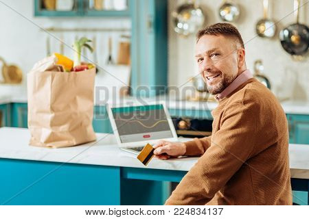 Non cash transaction. Joyful positive self employed man sitting in front of the laptop and using his credit card while making a non cash transaction
