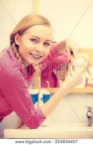 Young blonde woman applying moisturizing skin cream on face, looking in bathroom mirror. Girl taking care of dry complexion layering moisturizer. Skincare treatment