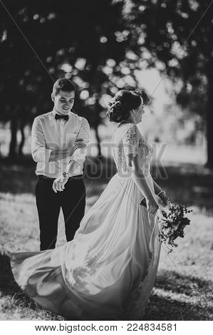 Black and white photo bride and groom in the background of park trees.