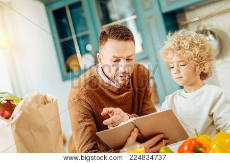 Home recipes. Nice pleasant handsome man standing near his son an holding a notebook while choosing a recipe together