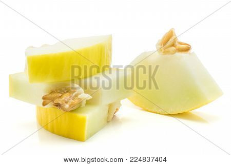 Yellow honeydew melon four cut pieces with seeds isolated on white background