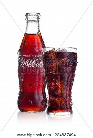 LONDON, UK - FEBRUARY 02, 2018: Cold bottle and glass of Diet Coca Cola drink with ice and dew on white background. The drink is produced and manufactured by The Coca-Cola Company.