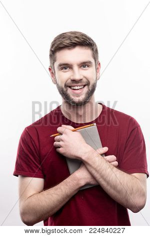 Treasured possession. Upbeat young man in a t-shirt pressing a daily planner and a pencil to his chest and smiling at the camera while posing isolated on a white background