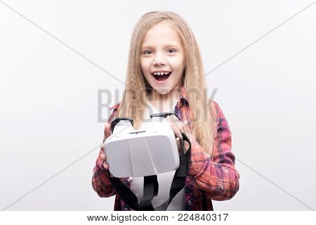 New toy. Upbeat adorable little girl holding a VR headset and smiling brightly while posing for the camera, standing isolated on a white background
