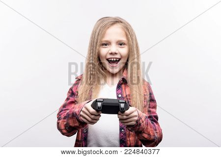 Binge playing. Adorable little girl playing video games with a controller and smiling widely while posing isolated on a white background