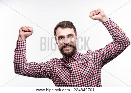 Long-awaited achievement. Charming bearded man raising his hands in triumph, having achieved success, and smiling brightly while posing isolated on a white background