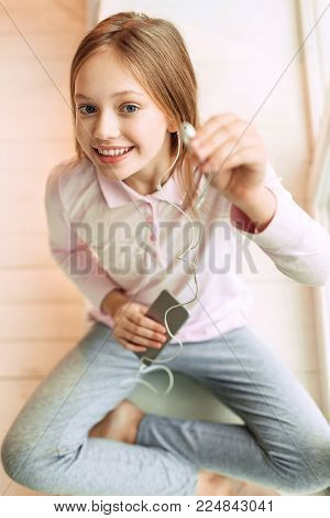 Give it a try. Top view of a cute teenage girl sitting cross-legged on the floor and suggesting listening to music, handing one earphone
