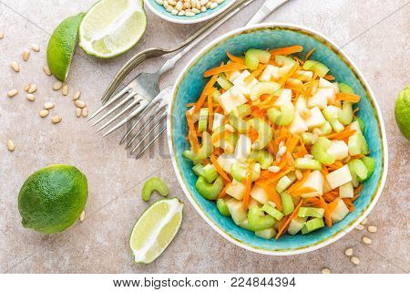 Salad with fresh celery, apple and carrot. Healthy vegetarian cuisine