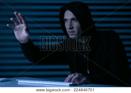 Excellent graphics. Nice focused male gamer rising hand while looking up and holding hand on keyboard
