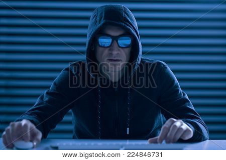 Final battle. Confident ambitious male gamer sitting at the table while dressing in hood and wearing glasses