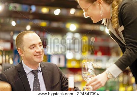 A barmaid girl carries a wine glasses on a tray to the client of the hotel bar. Focus on the man the client. The concept of service.