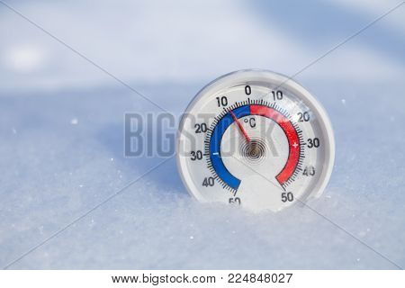Thermometer with celsius scale placed in a fresh snow showing sub-zero temperature minus 8 degree - cold winter weather concept