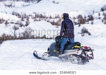Man rides on snowmobile in standing position through snowy fields. Winter adventures
