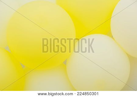 Close up of bunches and groups of yellow helium balloons.