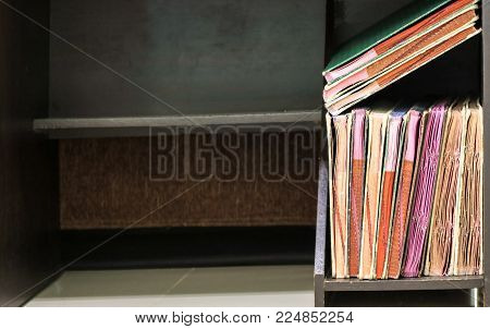Ancient books in blurred old bookcase, black cabinet