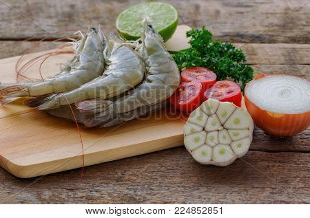 Fresh white shrimps on wood cutting board in side view. Prepared raw prawn or shrimps and vegetable and herbs for cooking. Fresh shrimp for cook seafood menu on wooden table. Homemade delicious food concept. Fresh shrimp prepared for cooking.