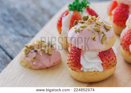 Strawberry choux cream. Combination with choux pastry whipped cream fresh strawberries glaze with white chocolate and chopped pistachios. Sweet and delicious dessert for Valentine. Homemade bakery. Strawberry cream puff for Valentines.