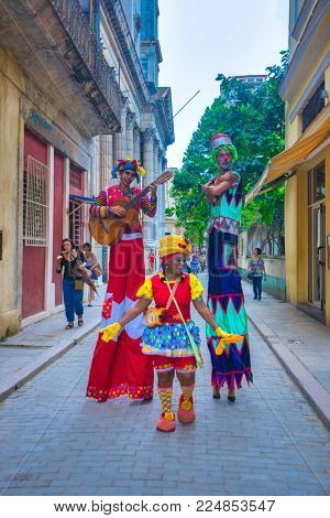 HAVANA, CUBA - DEC 06, 2015: Colorful stilt dancers in Old Havana street, the performers use public spaces like squares to interact with tourists and locals.