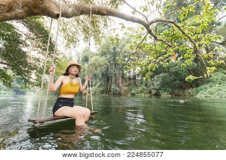 beauty asian woman in yellow knitwear and yellow hat and glasses sitting on cradle,it hanging on tree near stream