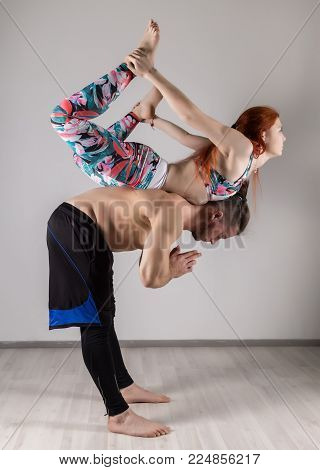 sports man and woman doing acroyoga exercises in a dark room. sports family concept