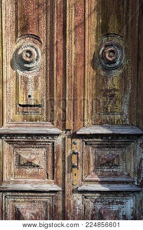 old wooden doors with a cracked paint, brightly lit in the form of a face or a mask