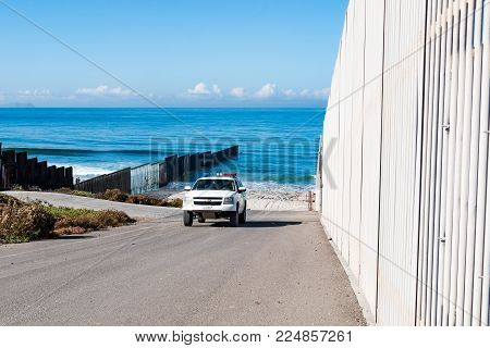 SAN DIEGO, CALIFORNIA - NOVEMBER 4, 2017:  A Border Patrol vehicle patrols between the inner and outer border walls near the Pacific ocean at Border Field State Park, by Tijuana, Mexico.